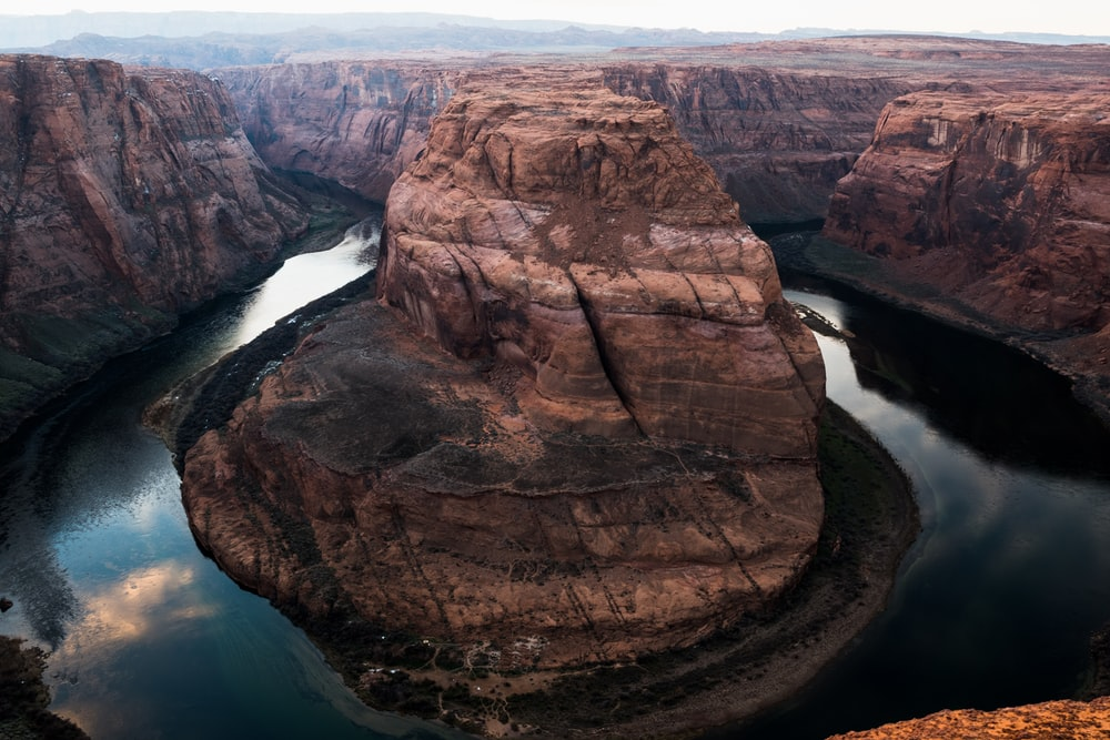 photo of brown buttes surrounded with river