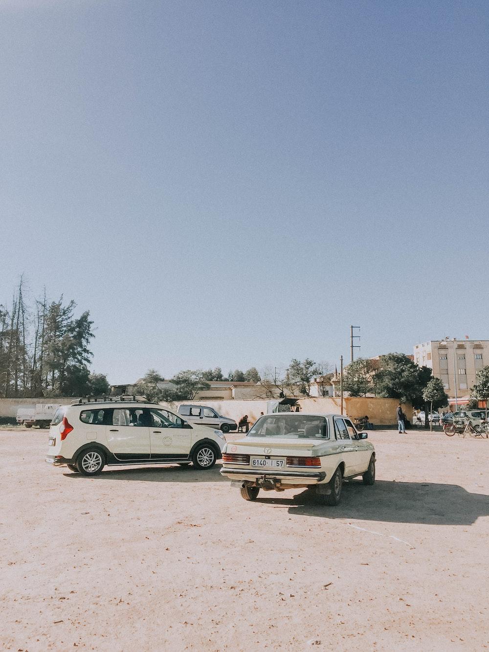 white sedan besides white 5-door hatchback