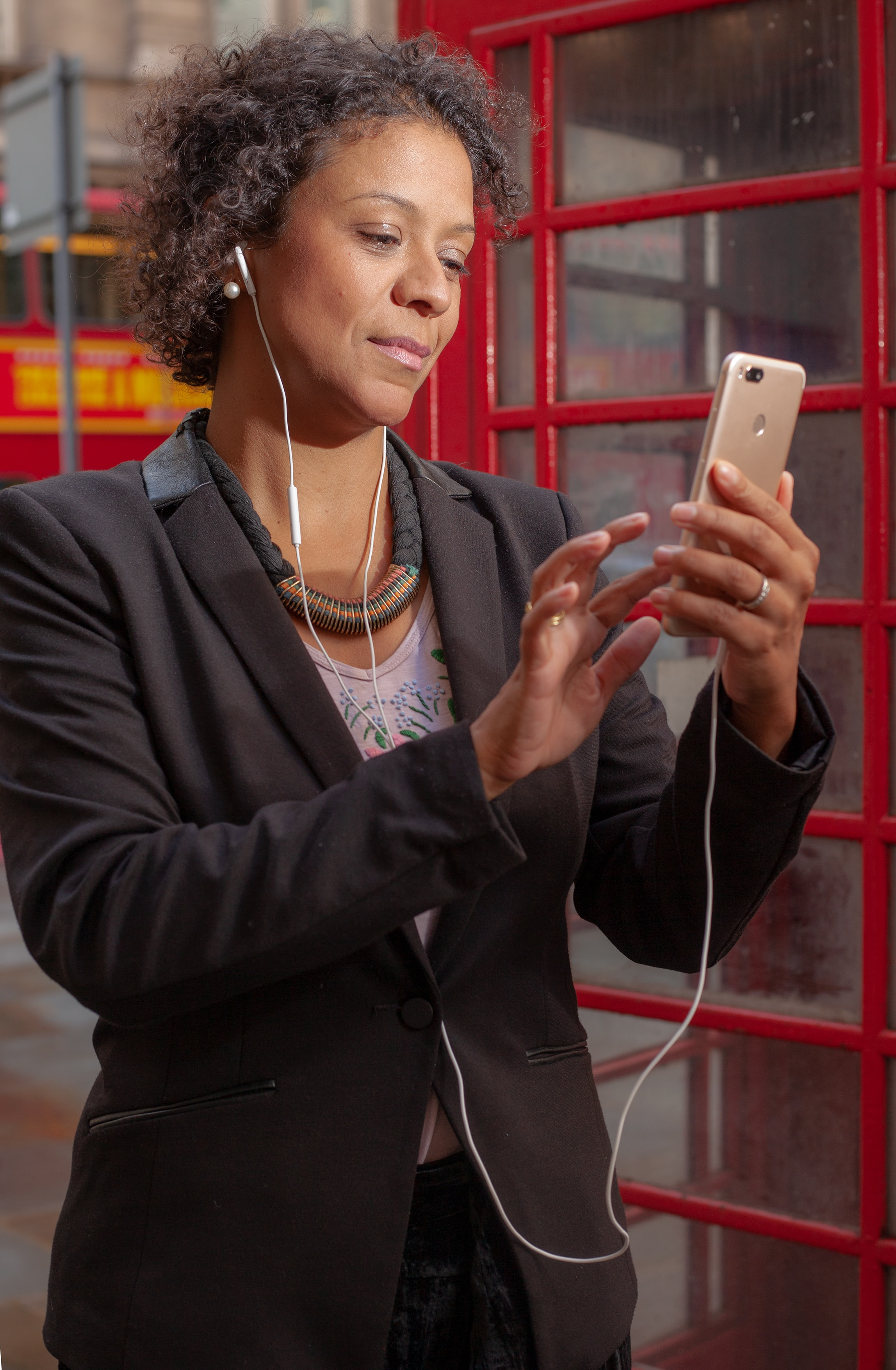 woman wearing earbuds while holding smartphone