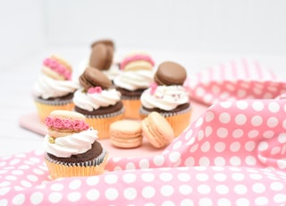 assorted macaroons and cupcakes on pink textile