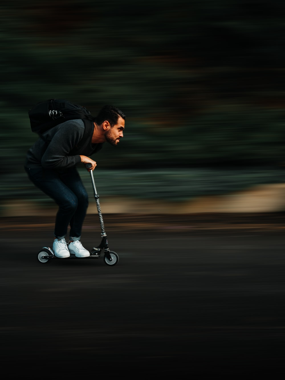 grown man riding very small electric kick scooter with fast speed