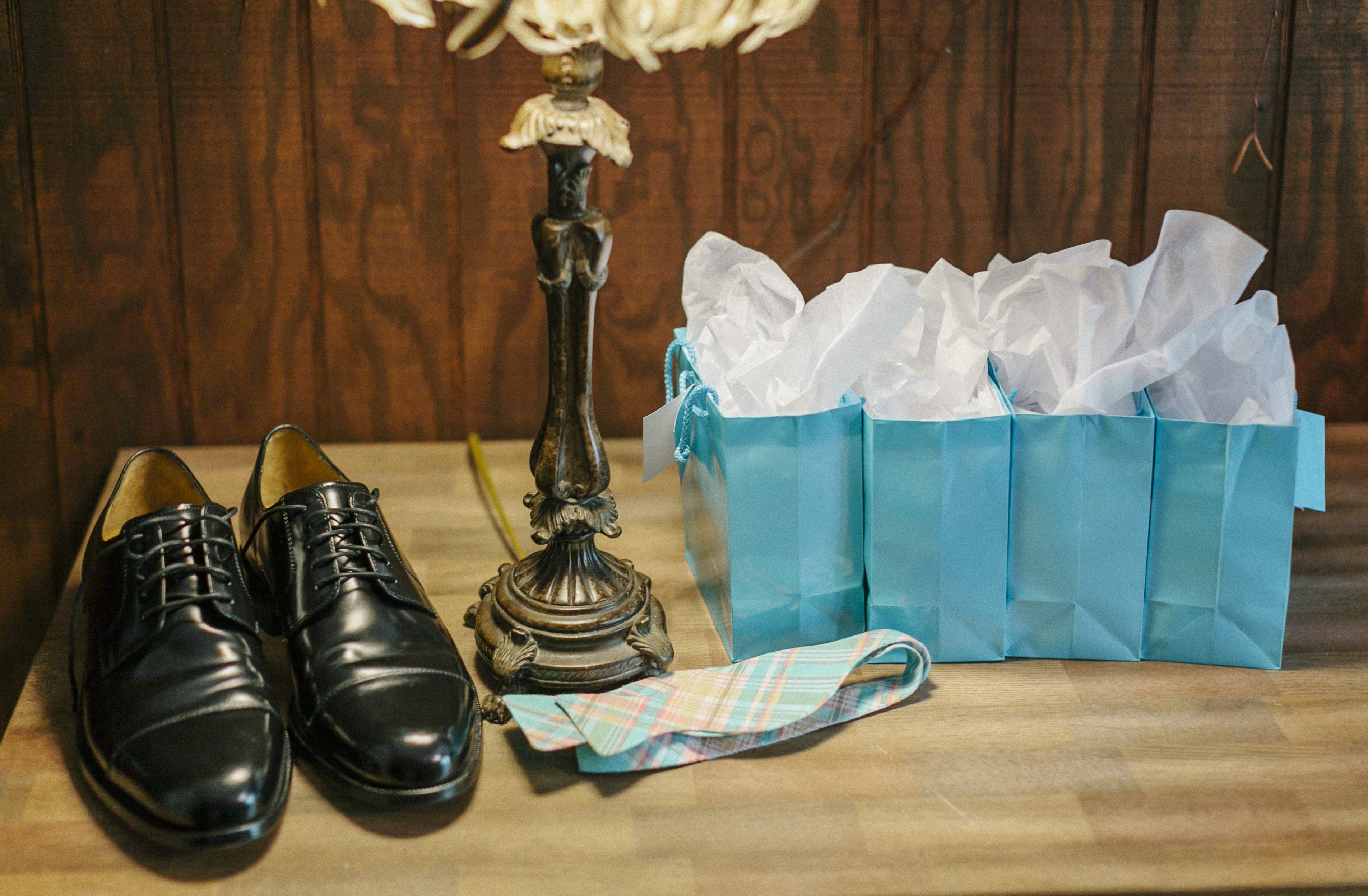 pair of dress shoes and desk lamp on table