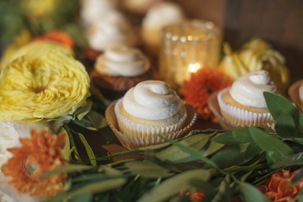 baked cupcake beside yellow and orange flowers