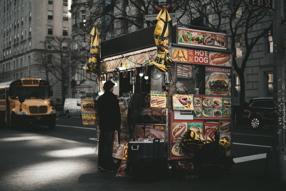 man standing in front of food cart at night time