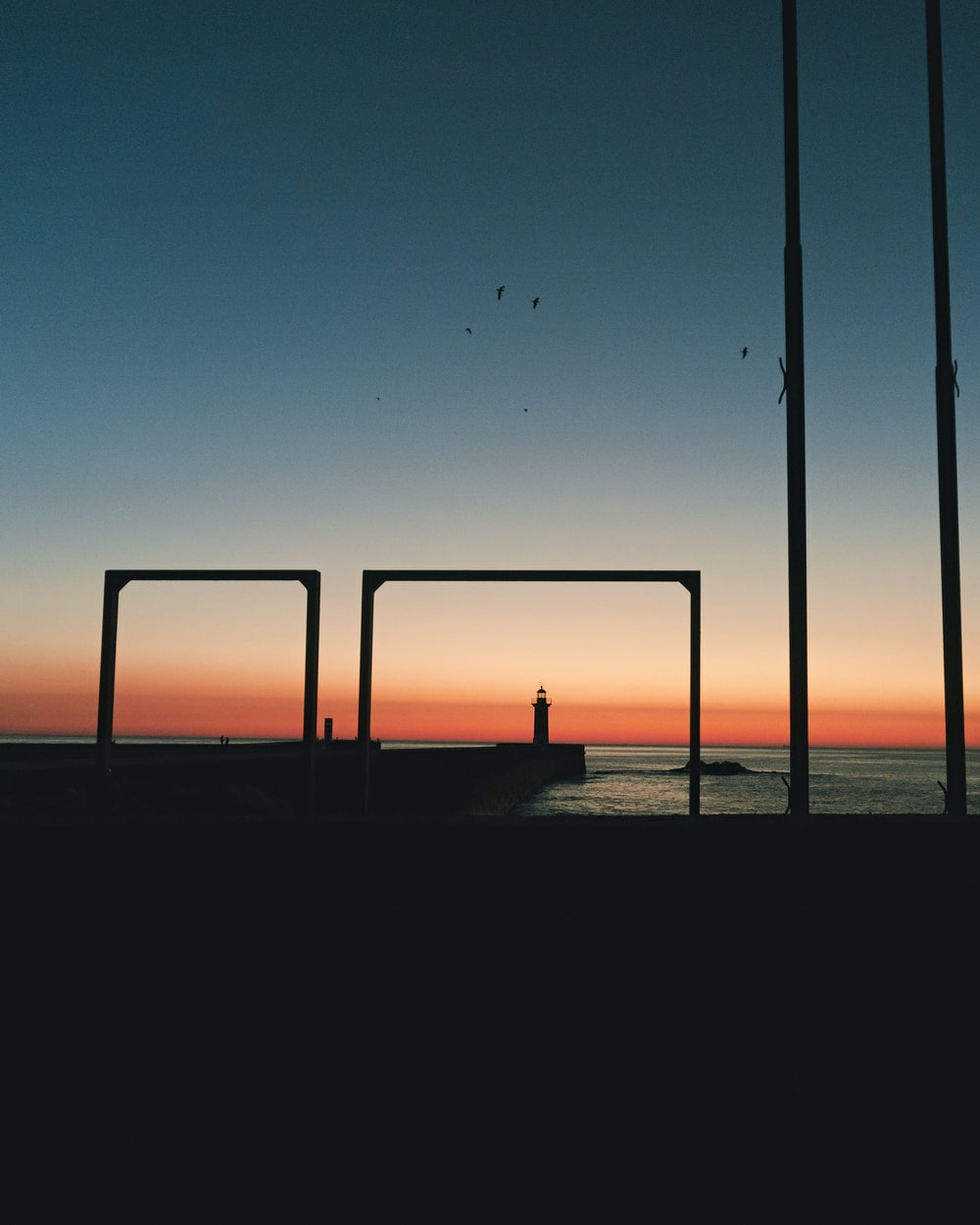silhouette of empty dock in front sea