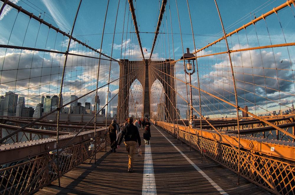 people walking on bridge under blue sky during daytime