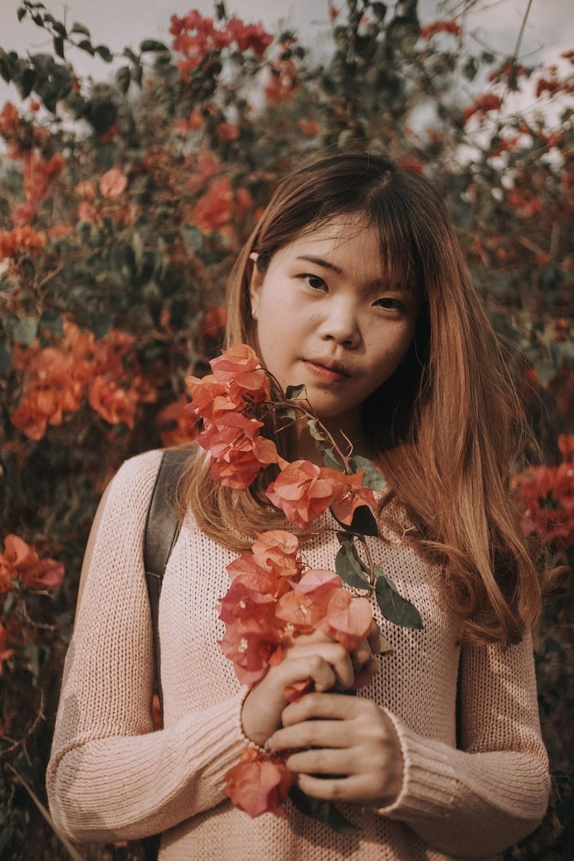 girl holding pink petaled flower at daytime