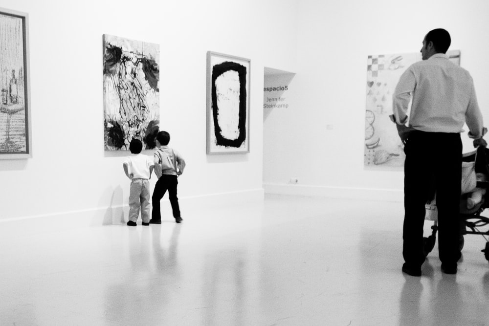 grayscale photography of two boys looking painting