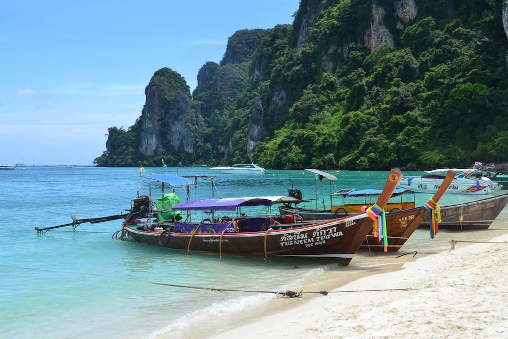 three passenger boats on seashore
