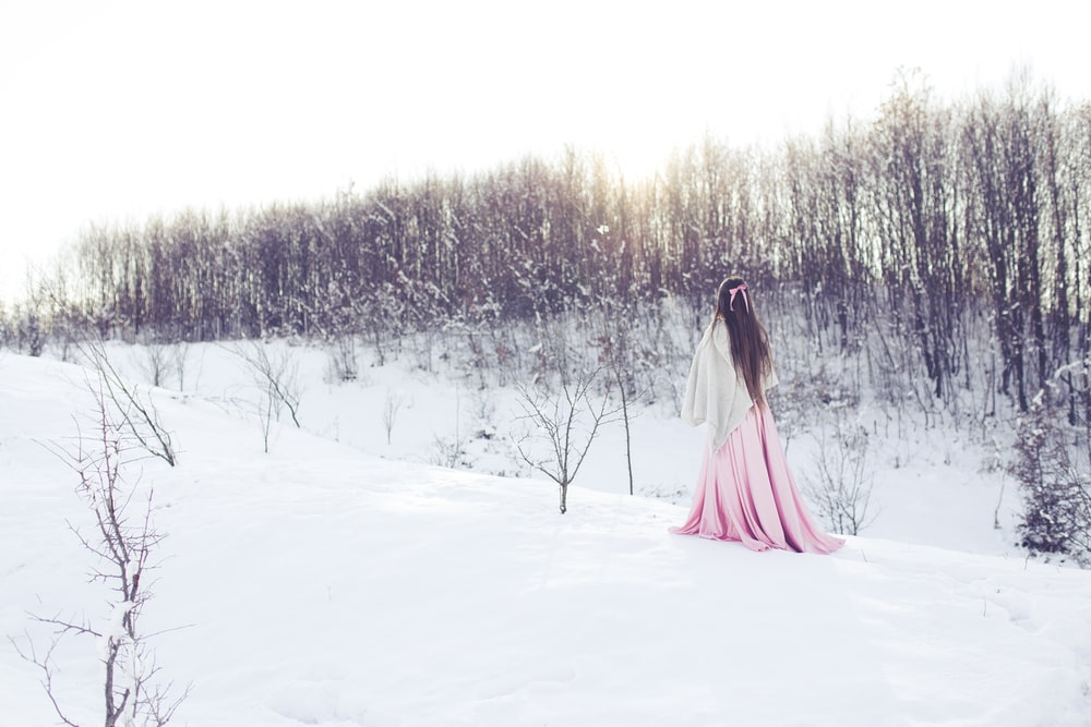 woman walking beside withered trees covered with snow