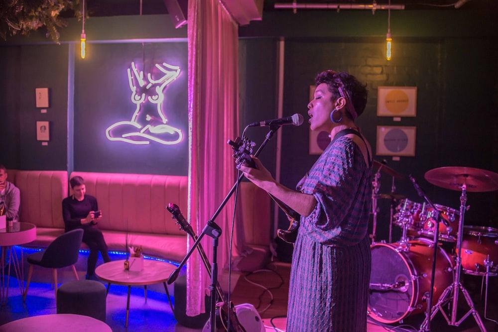 woman singing while playing guitar