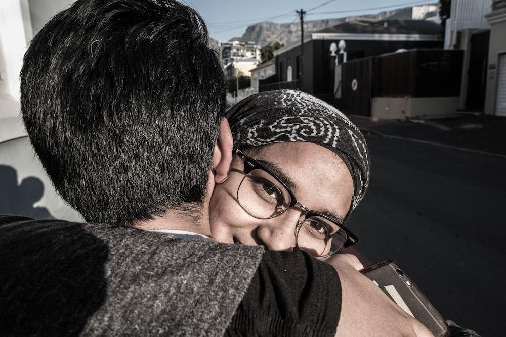 woman hugging man beside street during daytime