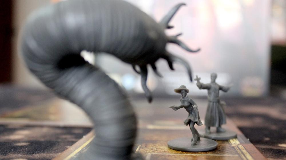 macro photography of gray figurines