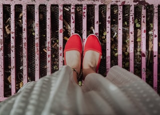 woman standing on pink grill wearing red flats