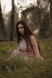 woman siting on grass during daytine