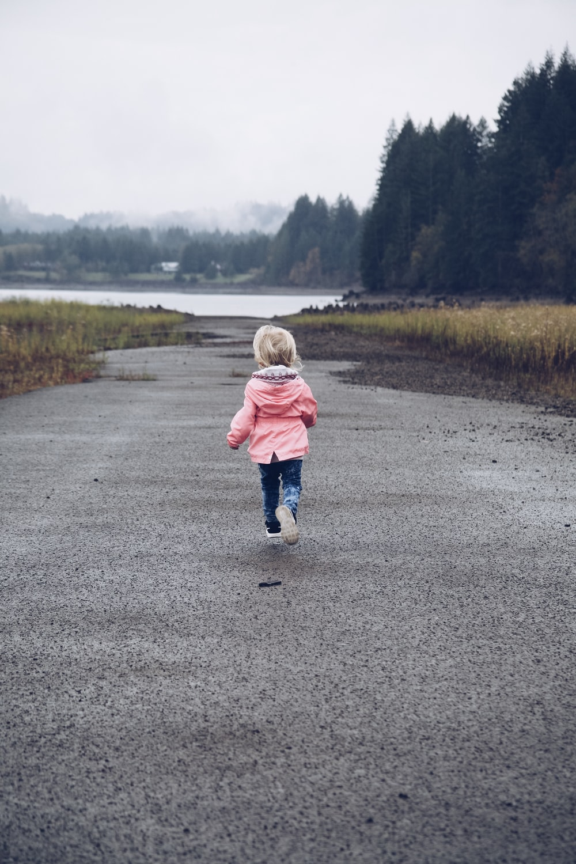 child running at road between grasses