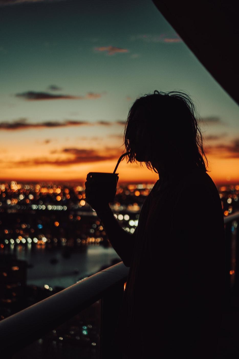 Mensch trinkt Mate Tee vor einer abendlichen Skyline