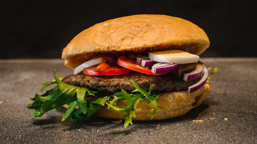 burger with potty, tomato, and onion