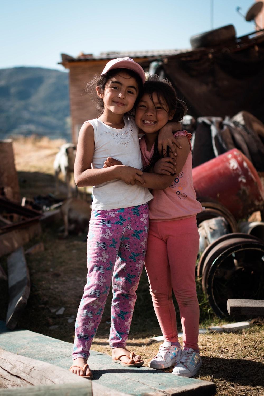 two girls hugging beside metal tool part