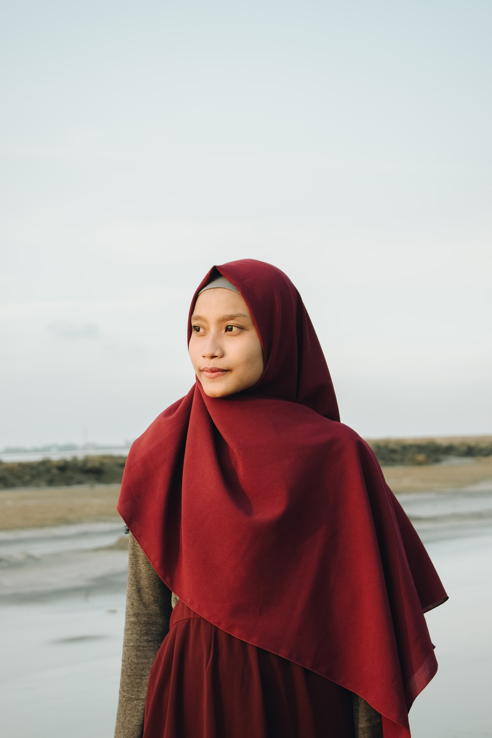 woman in red hijab standing beside plant