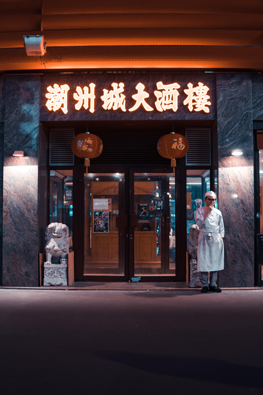 man in white top standing near at door