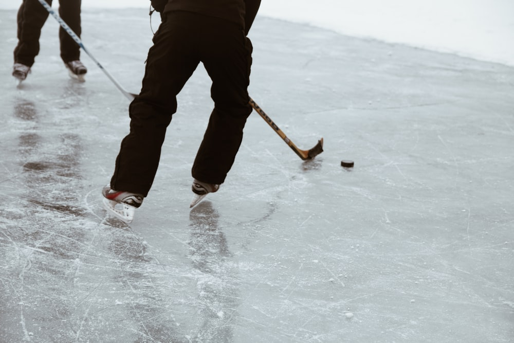 two persons playing hockey on ice field
