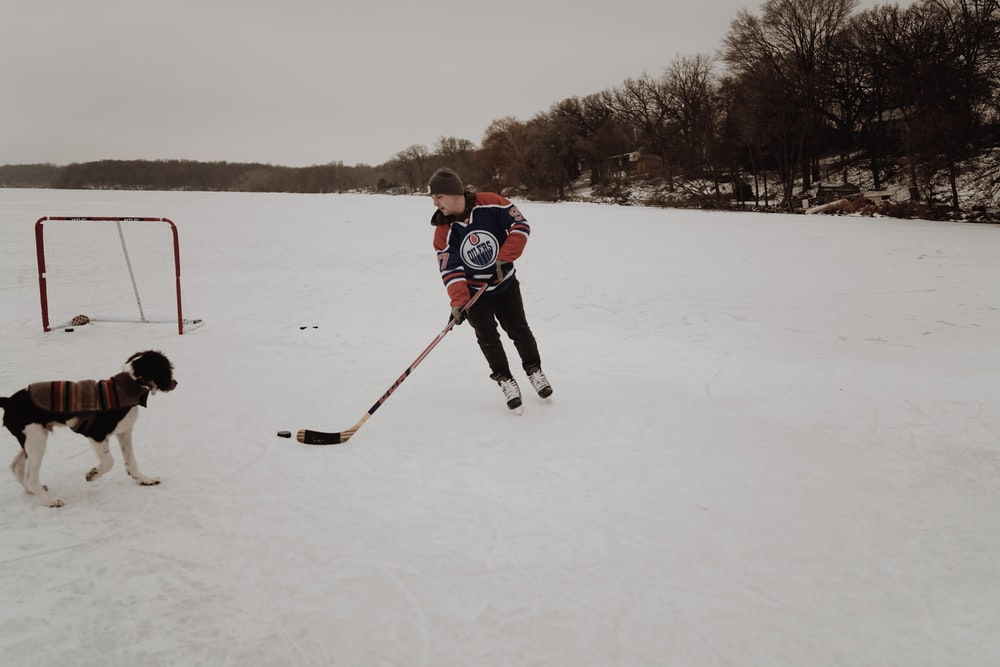 man playing ice hockey on snow covered field
