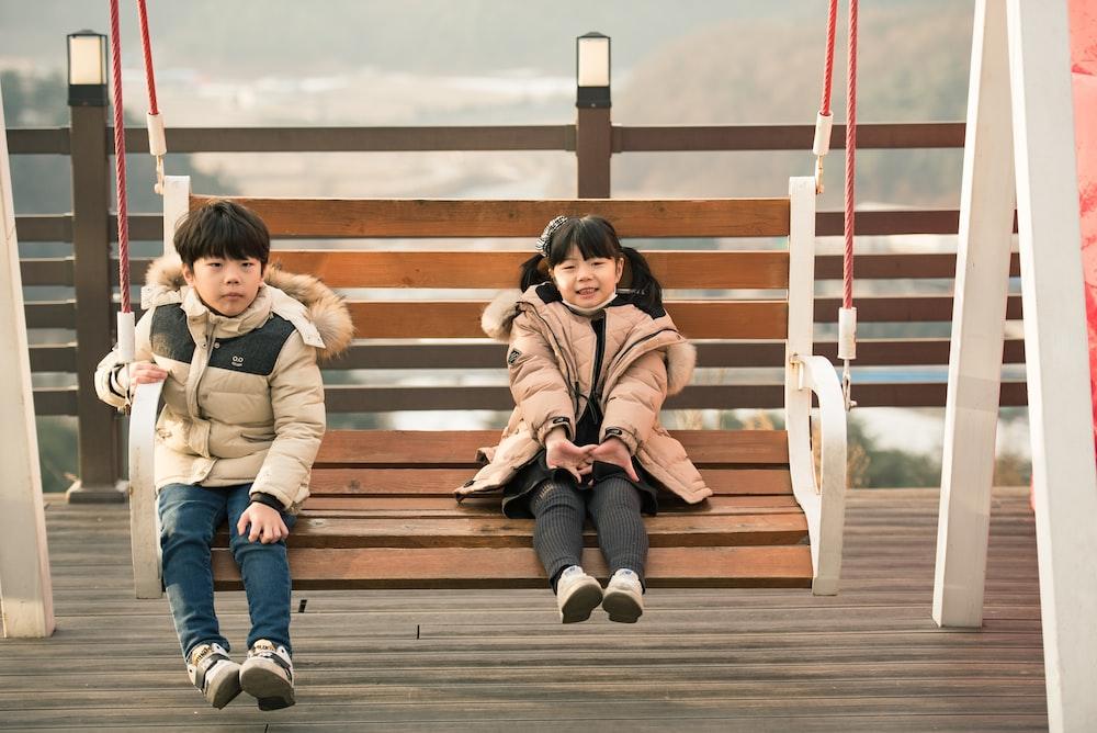 two children sitting at hanging bench