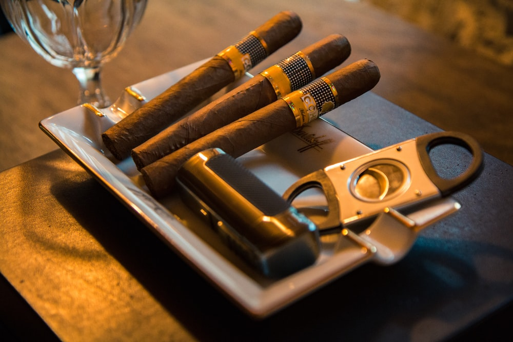 three cigar beside cutter on ashtray
