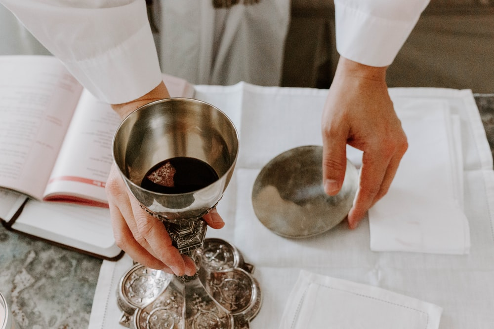 person holds chalice with liquid on table