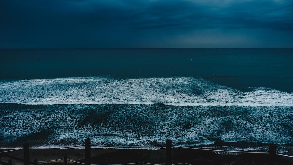 big waves overflowing the at barrier under dark sky