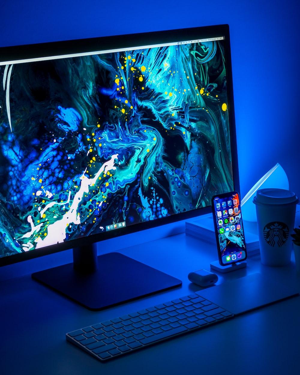 flat screen computer monitor turned on beside black keyboard