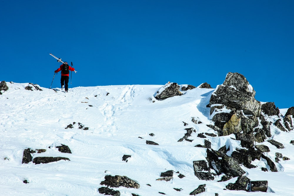 man carrying ski blades at top of mountain