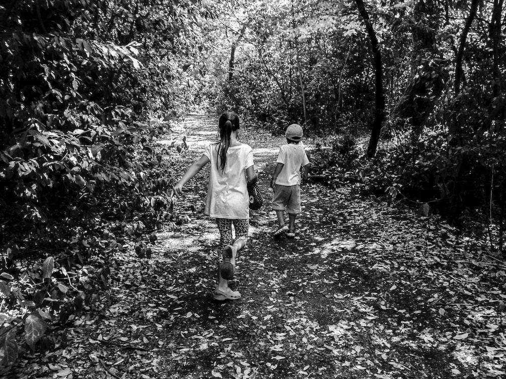 grayscale photo of boy and girl walking