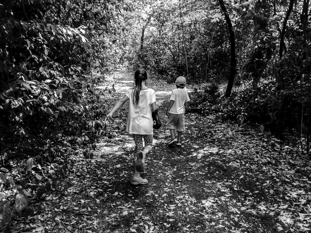 grayscale photo of boy and girl walking
