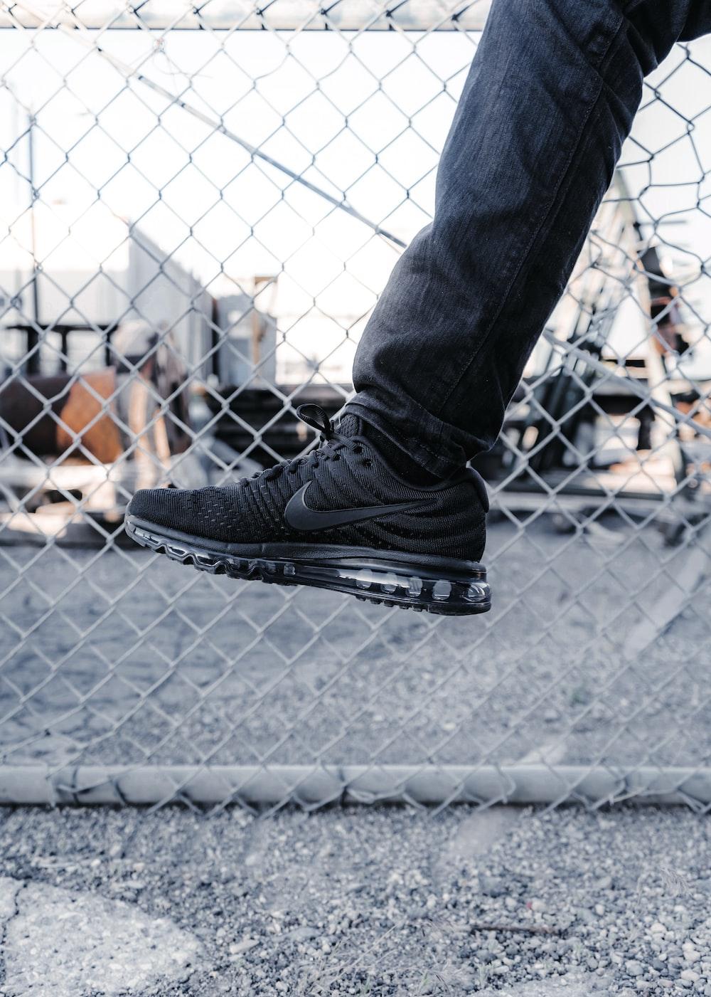 person wearing black Nike running shoe