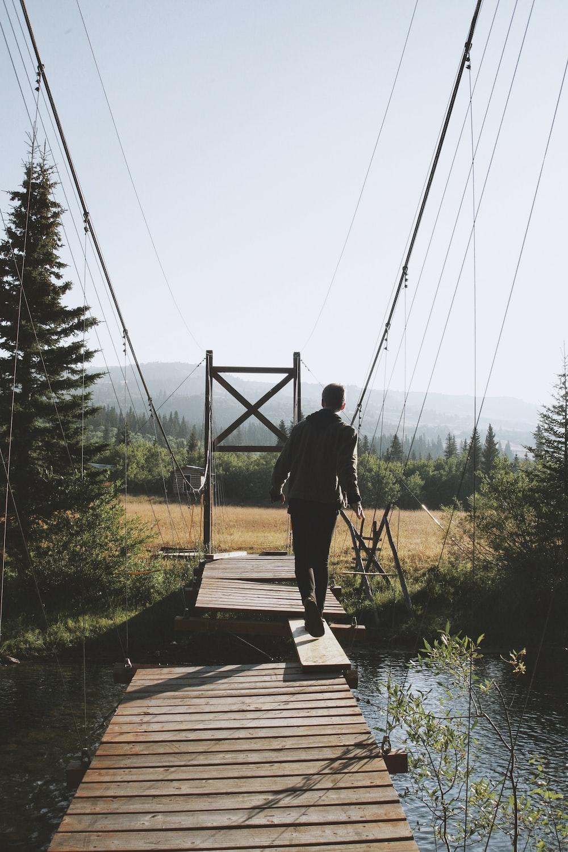 man walking on plank to cross bridge during daytime