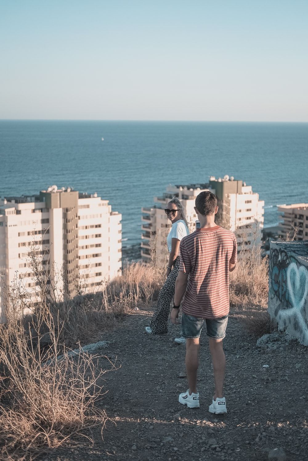 man takes photo of woman in white shirt near building overlooking sea