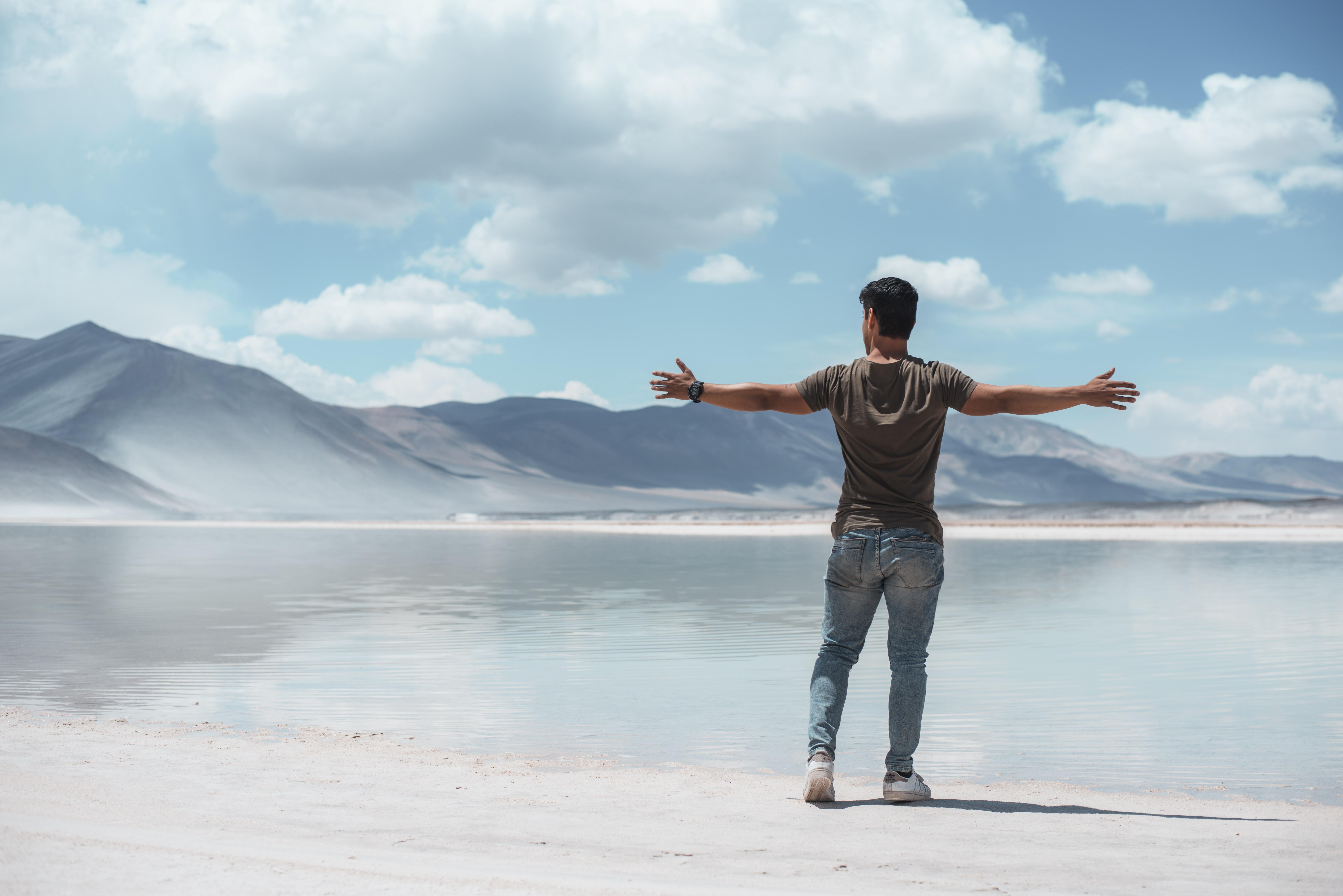 man opening his hands standing beside sea