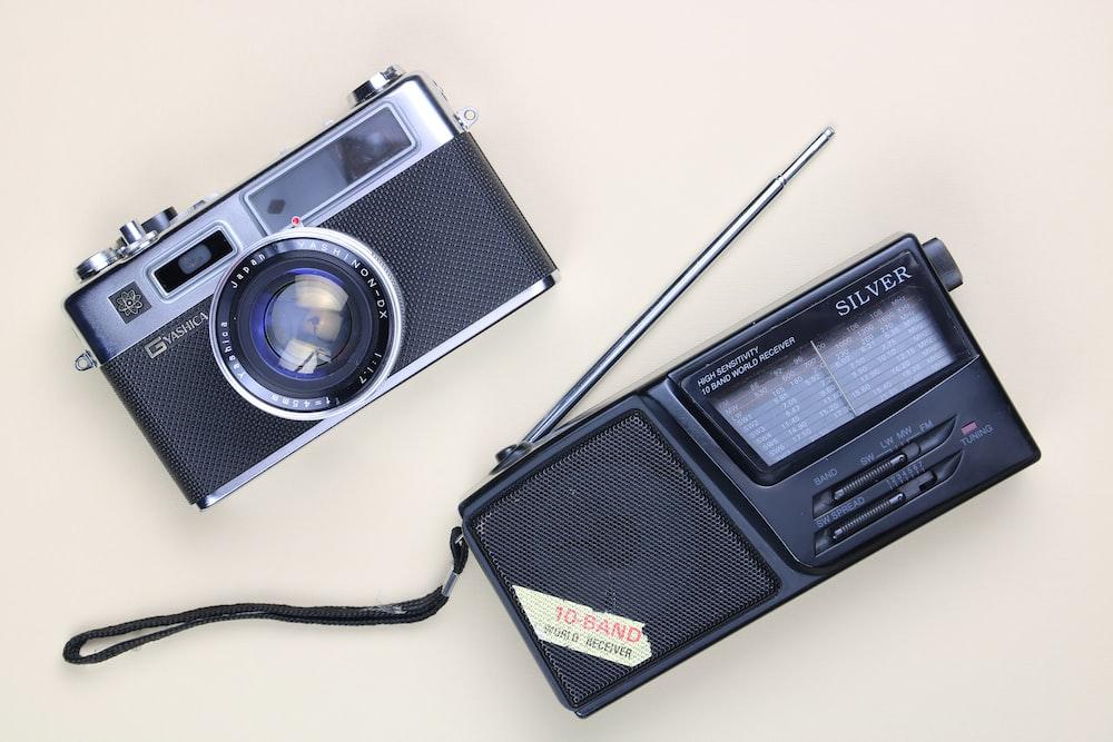 black and silver camera and portable radio