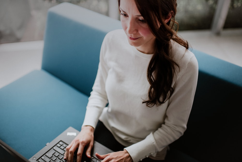 woman sitting on sofa while surfing on laptop