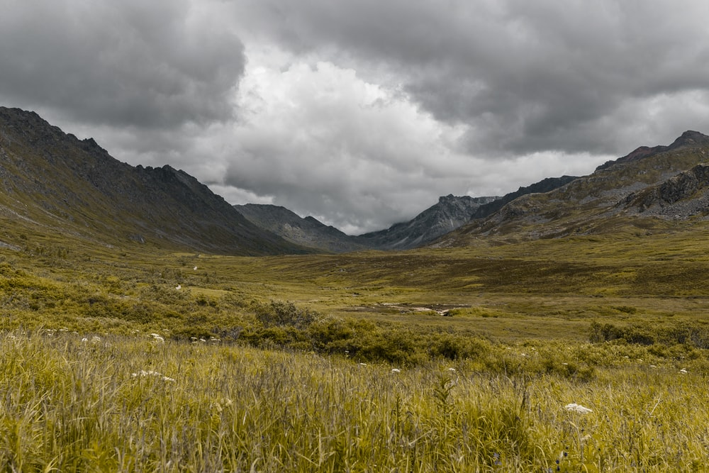 grass field between mountains on cloudy day