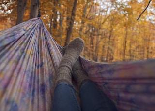 person lying wearing gray socks lying in multicolored hammock