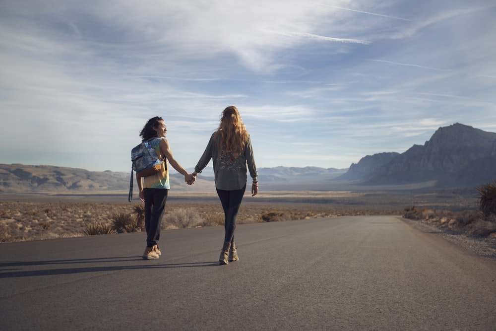 two man and woman walking on asphalt road
