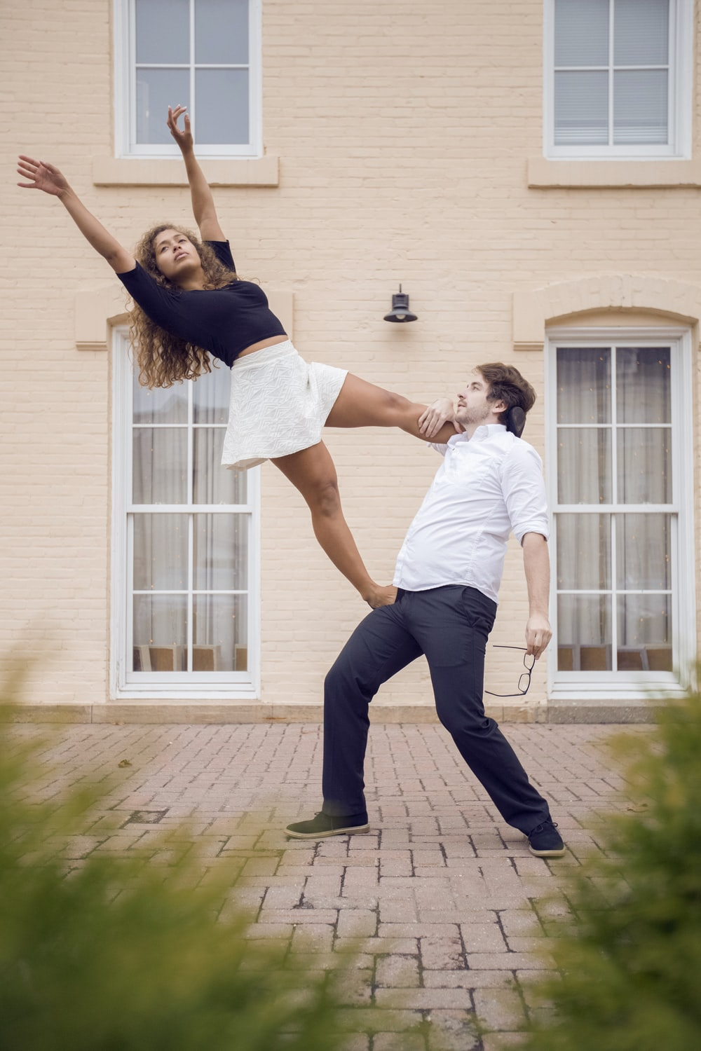 woman stepping on man while posing near building during daytime