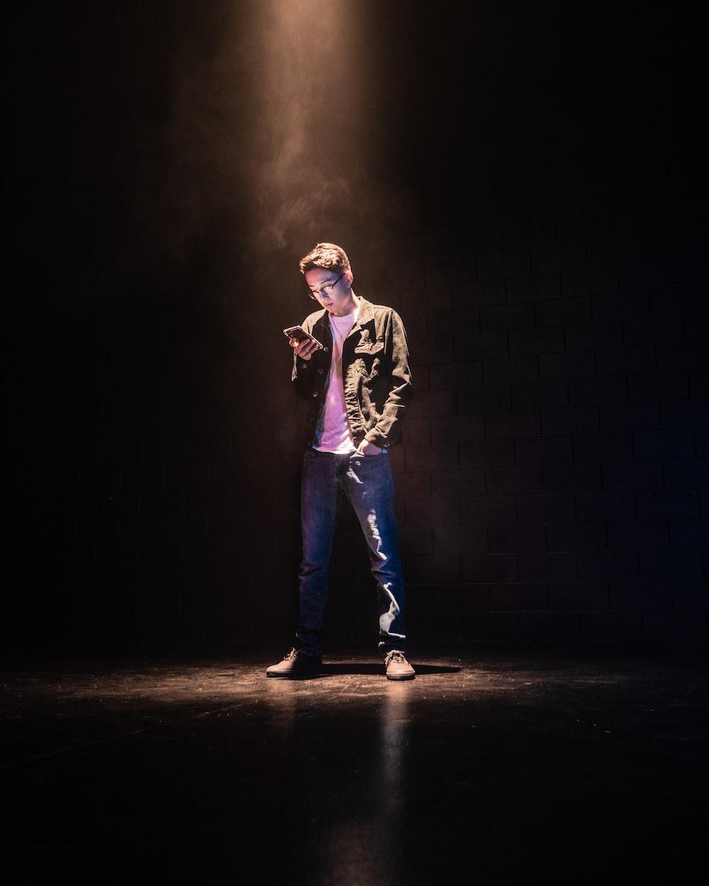 man standing on spotlight using smartphone