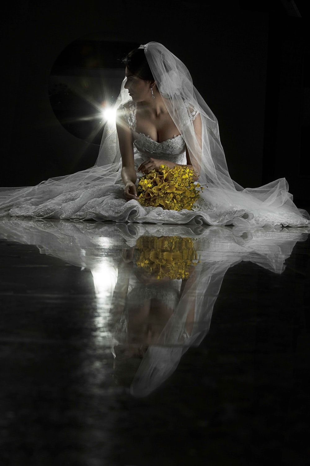 woman in white sleeveless wedding dress holding yellow bouquet of flowers