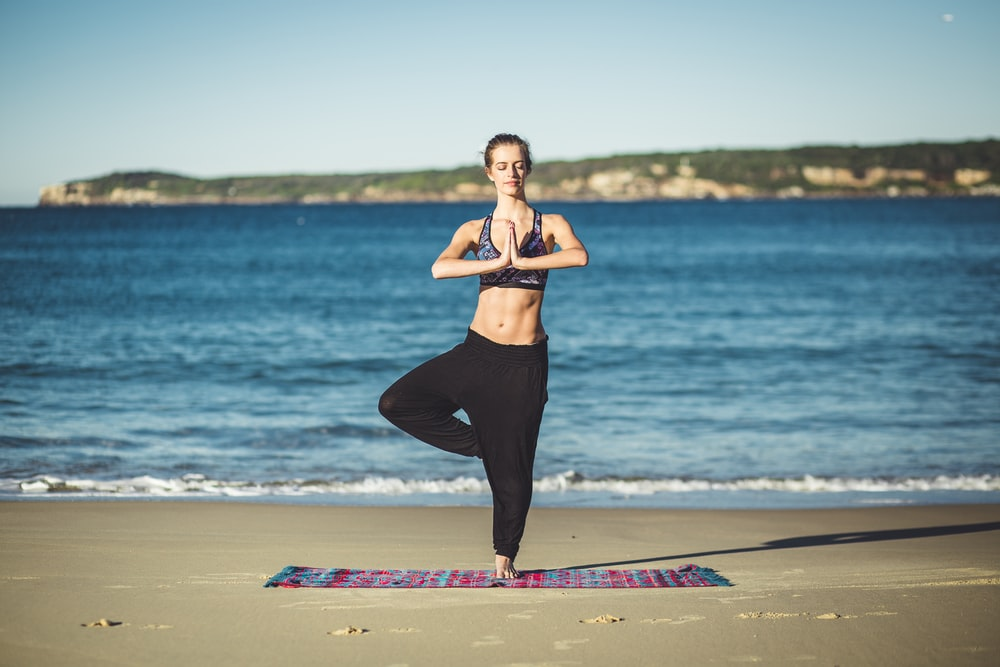 woman performing yoga on shore during daytime
