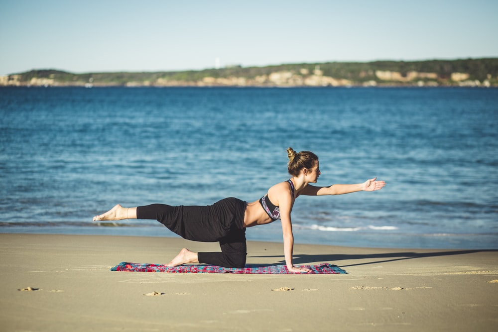 woman doing yoga on seashore