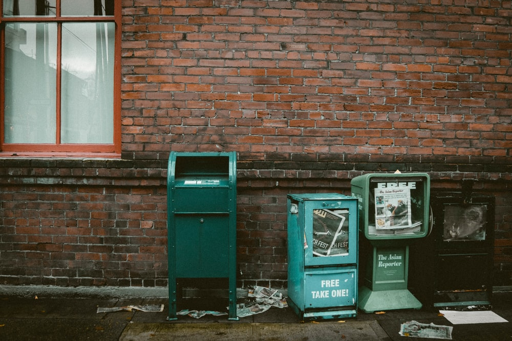 blue garbage bin beside brown bricked wall during daytime